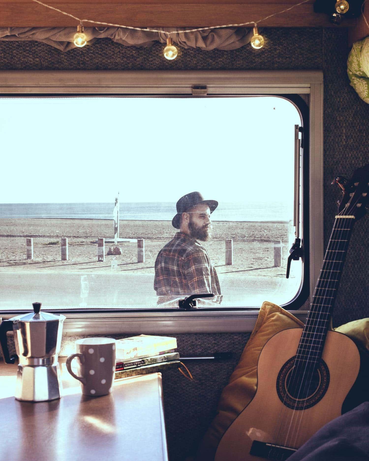 chico con sombrero a través de ventana de una caravana