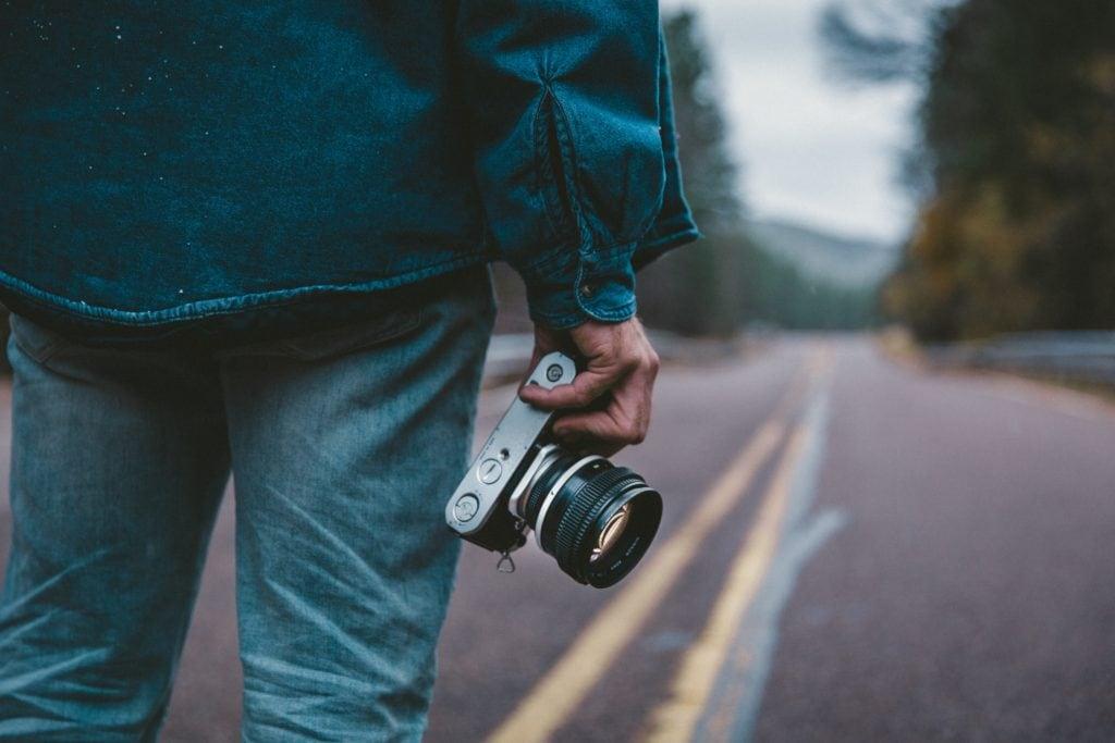 Cámara fotográfica en la mano con carretera de fondo
