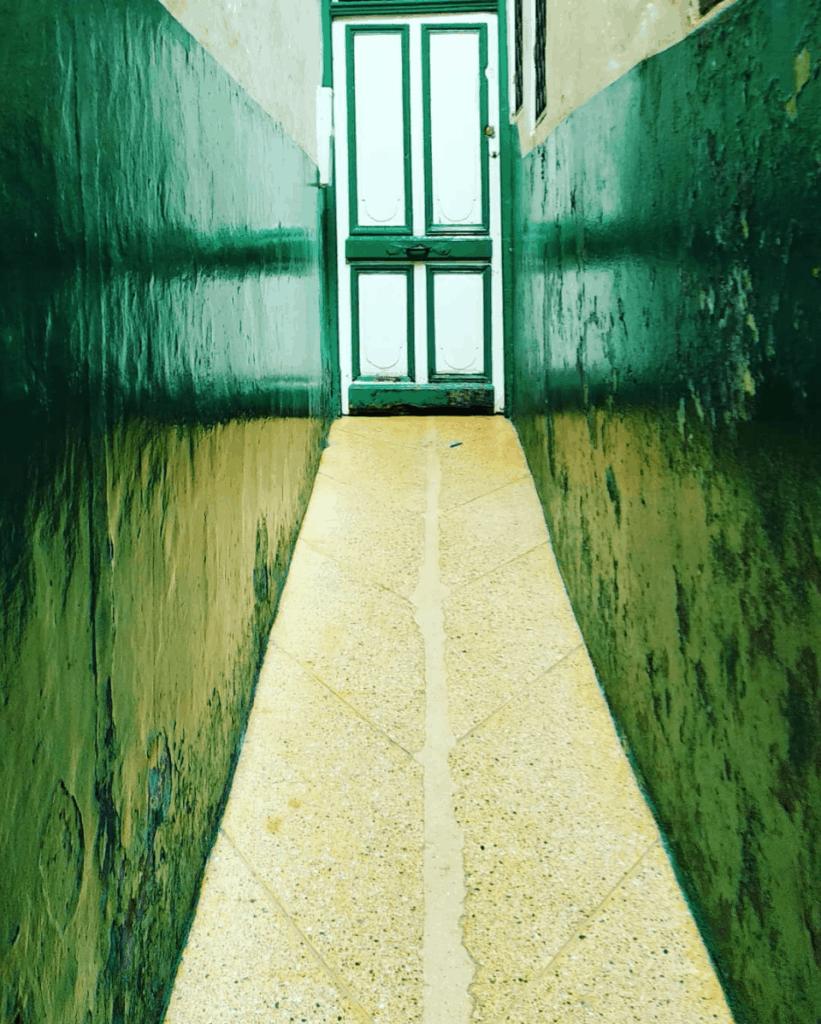 pasillo con puerta verde al fondo