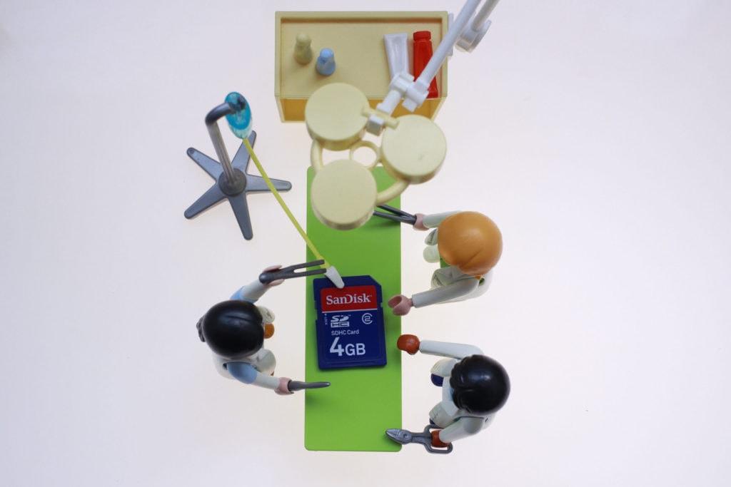 Muñecos arreglando una tarjeta de memoria sobre fondo blanco iluminado