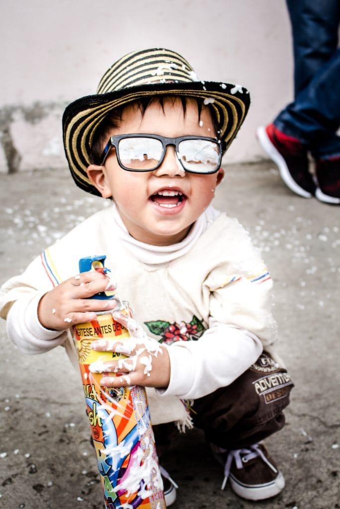 niño con gafas de sol jugando con espuma