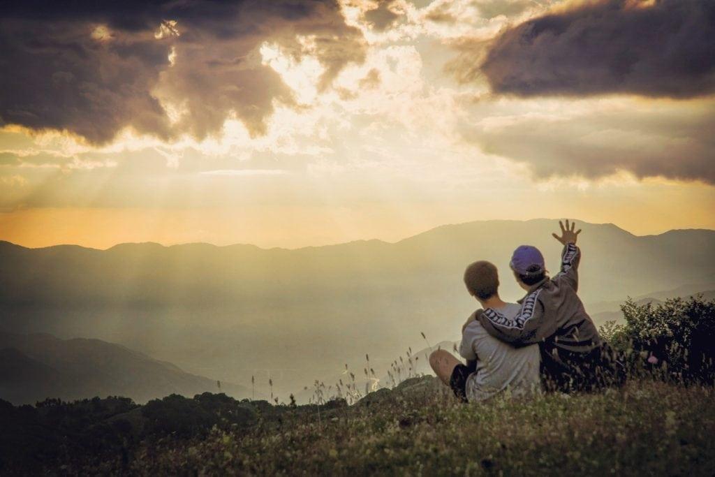 Padre e hijo en montaña mirando al horizonte