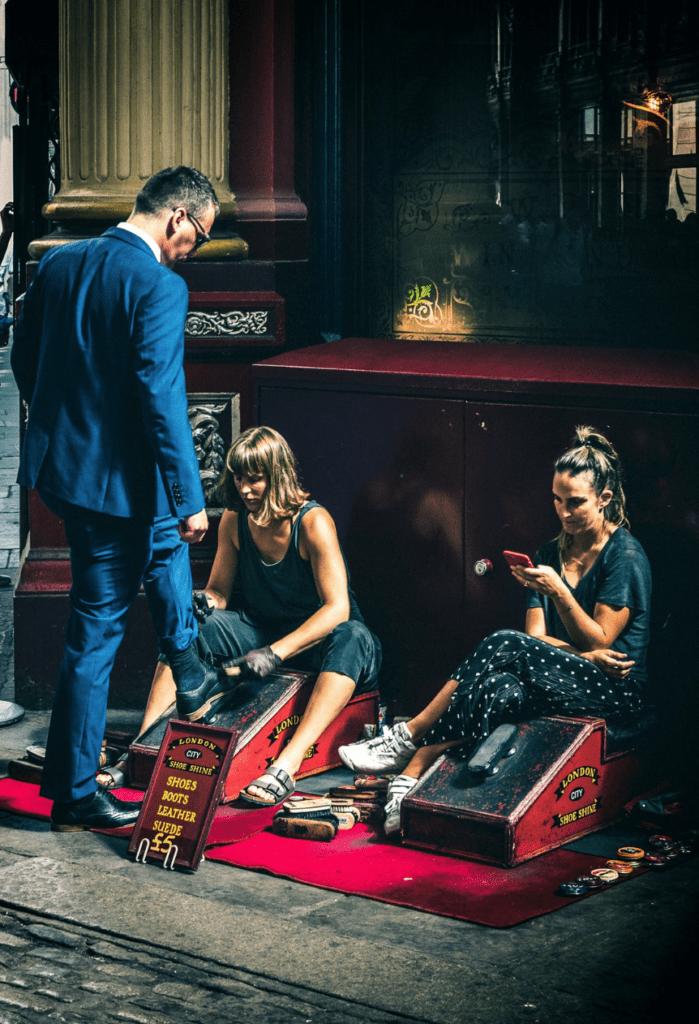 Escena callejera, mujer limpiando zapatos