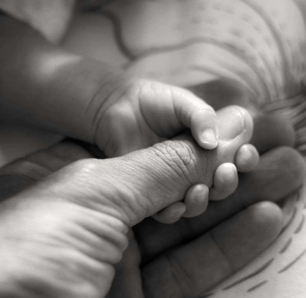 Bebé agarrado al dedo de su papá