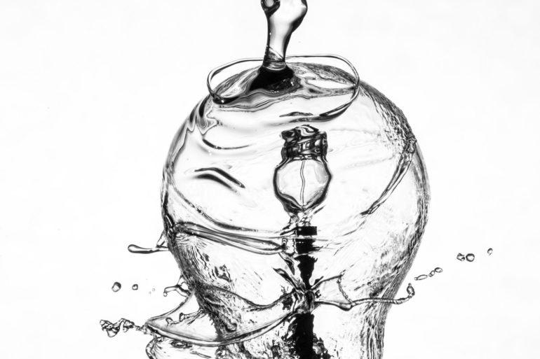 Bombilla bañada por chorro de agua sobre fondo blanco