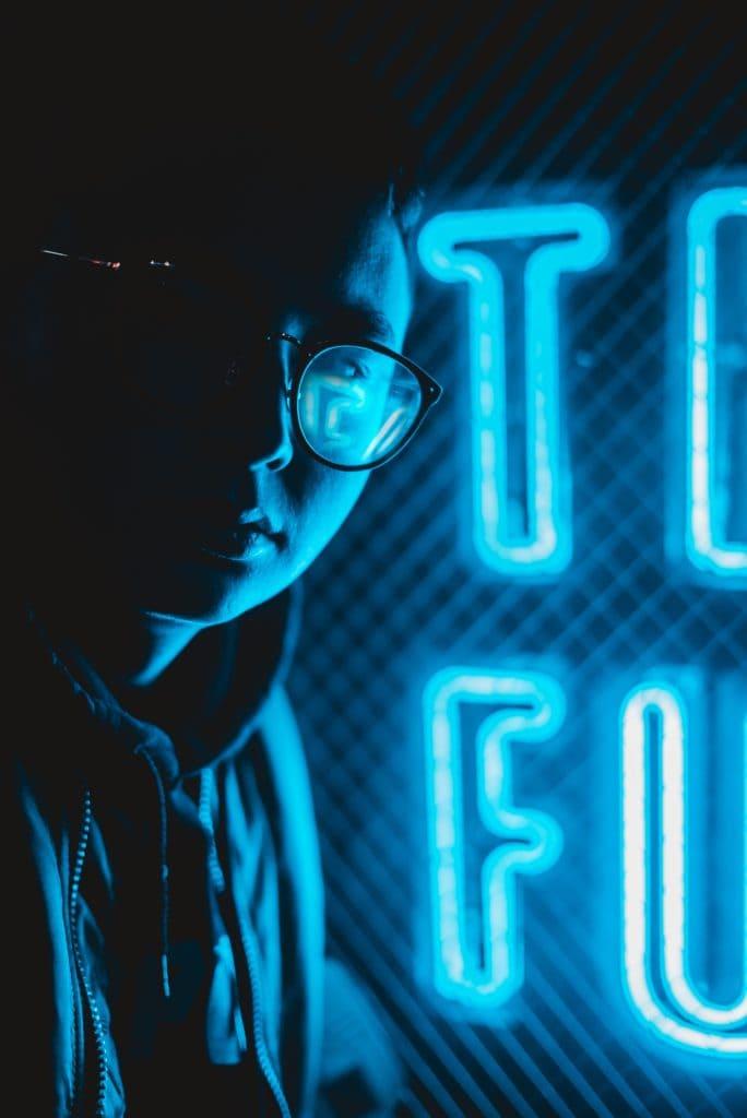 chico con luces de neón azules al fondo