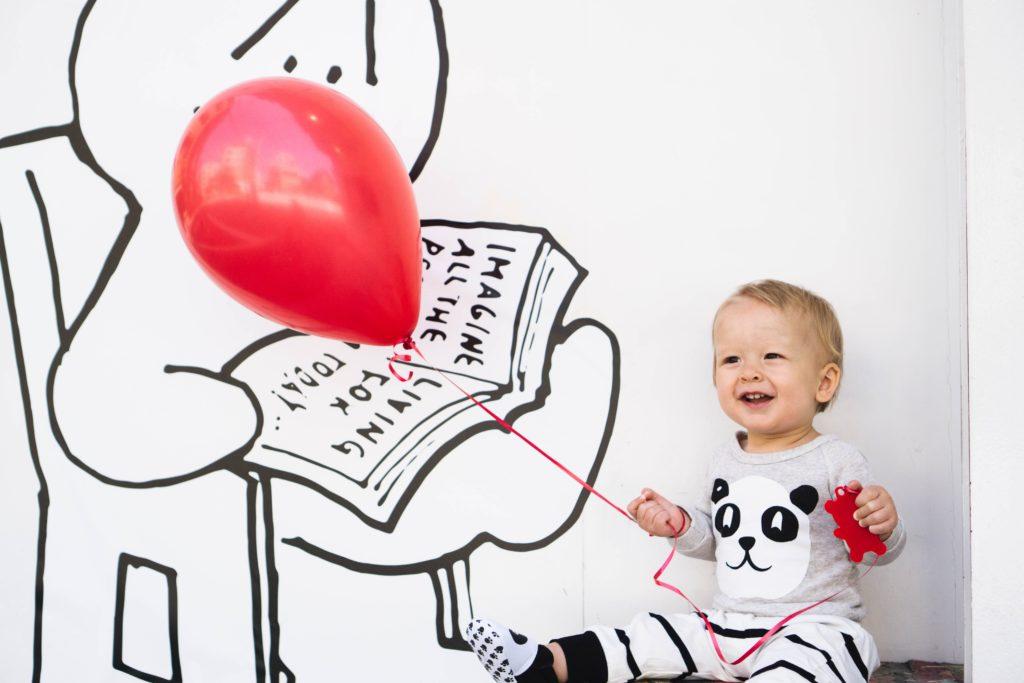 bebé con globo rojo
