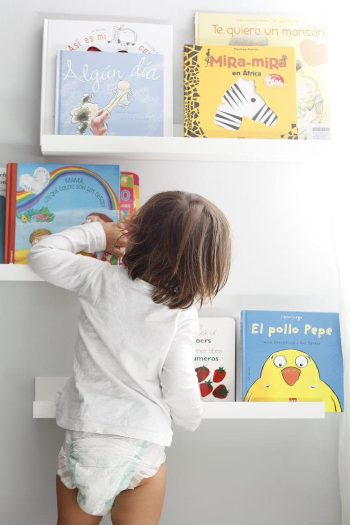 bebé con pañal buscando libro