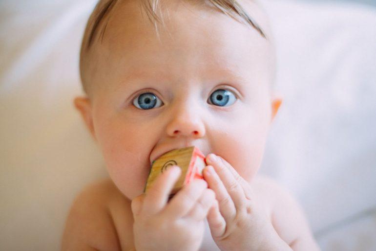 Bebé mirando mientras muerde juguete