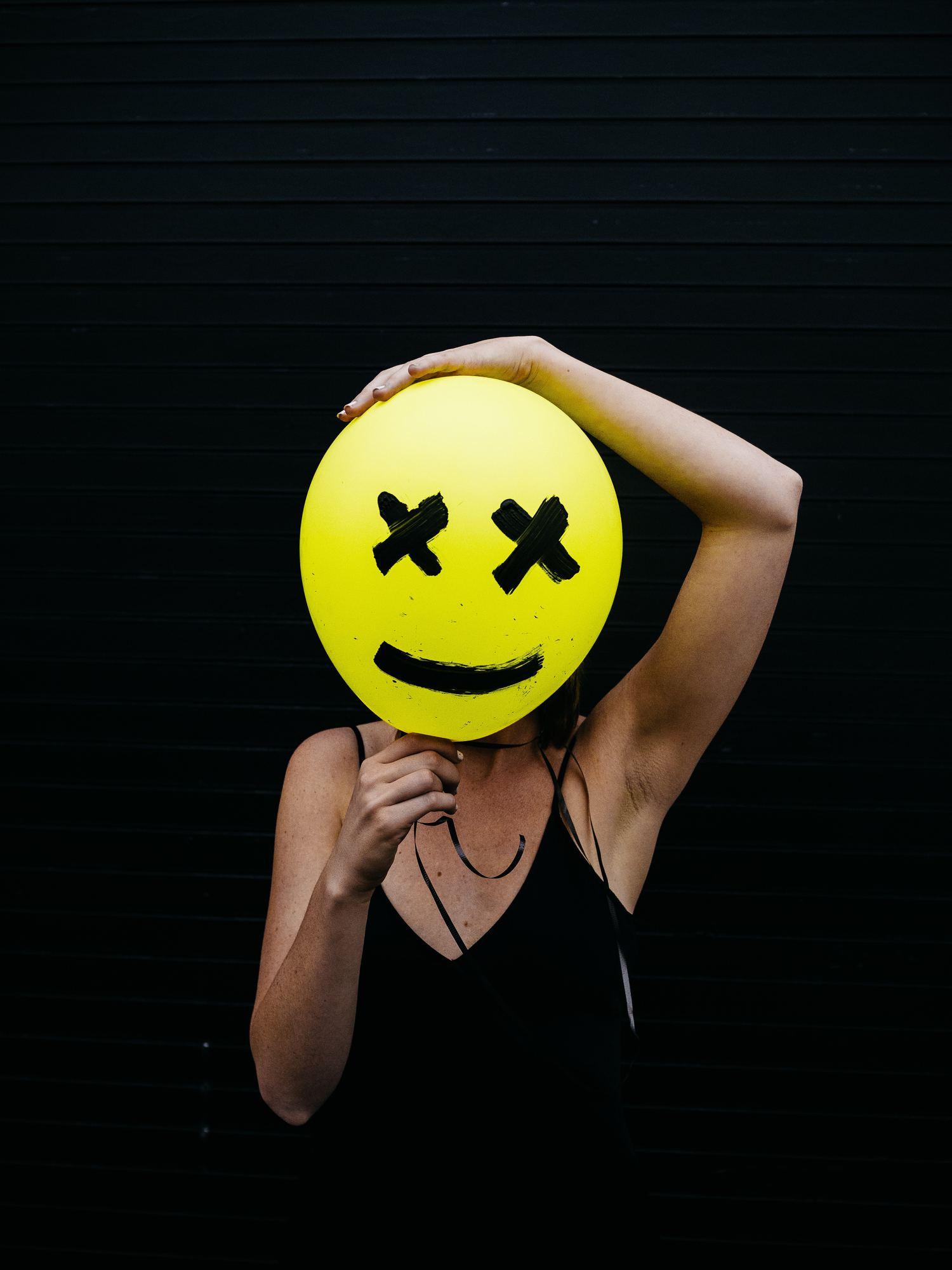 retrato con cara en forma de emoticono pintado en un globo