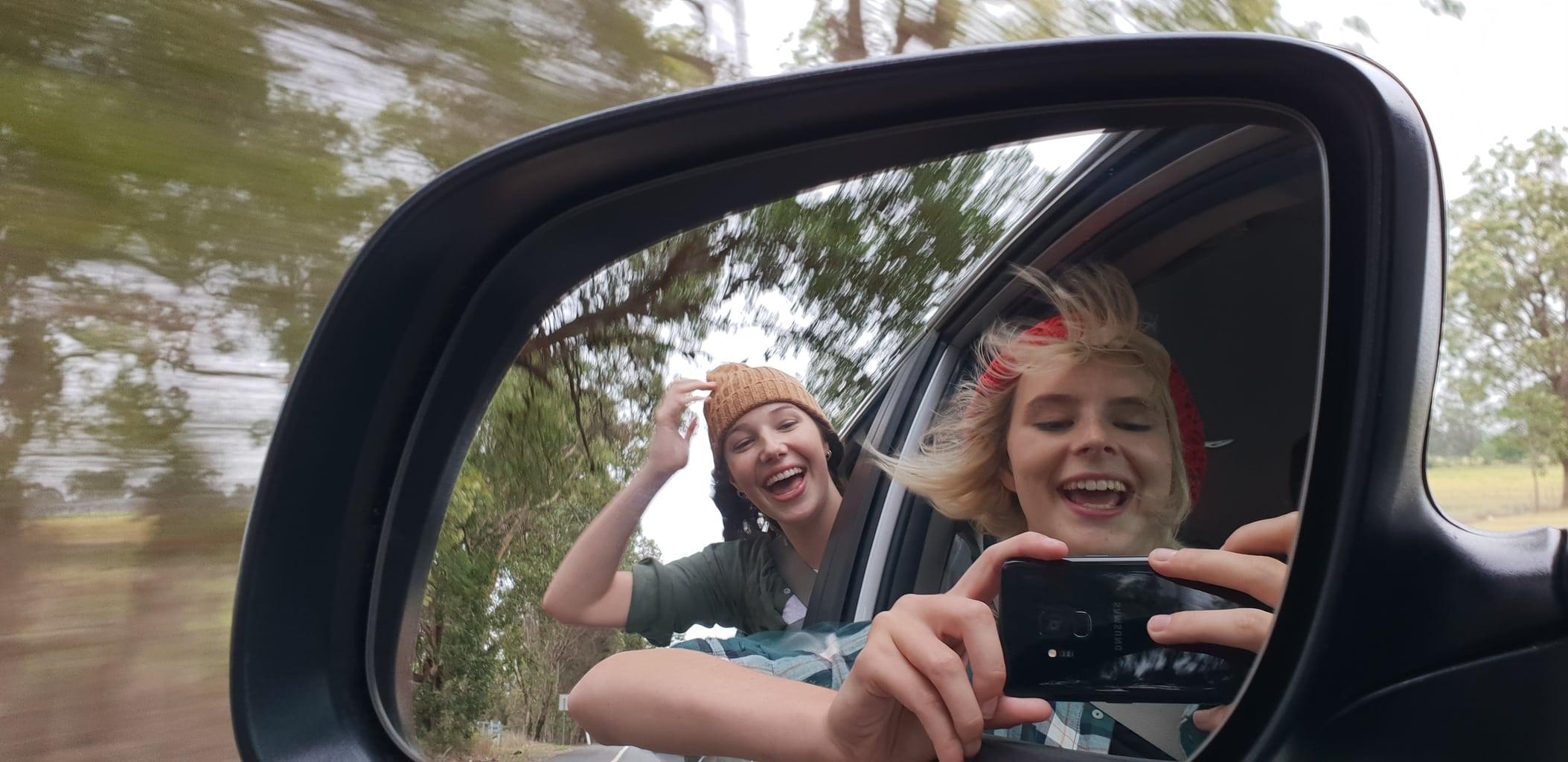 Jóvenes sonrientes en retrovisor de coche con Galaxy S9