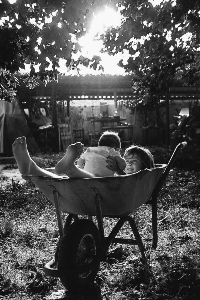 Hermanos pequeños tumbados en una carretilla