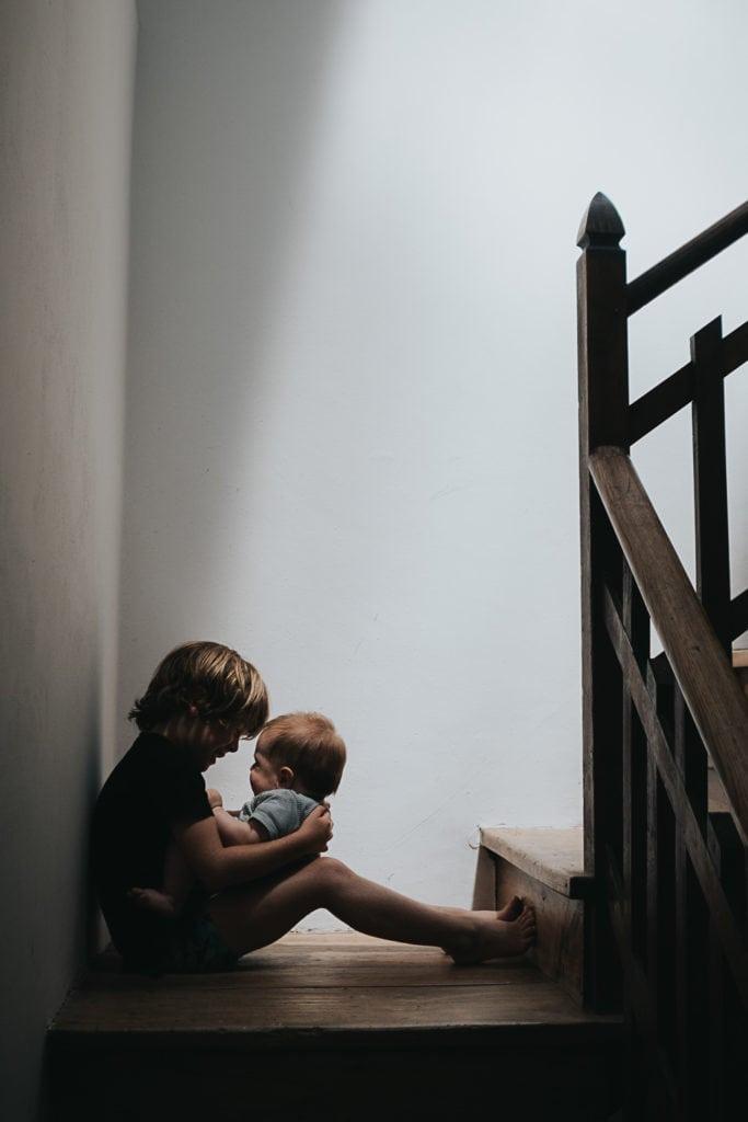 Bebé en brazos de su hermano sentado en una escalera