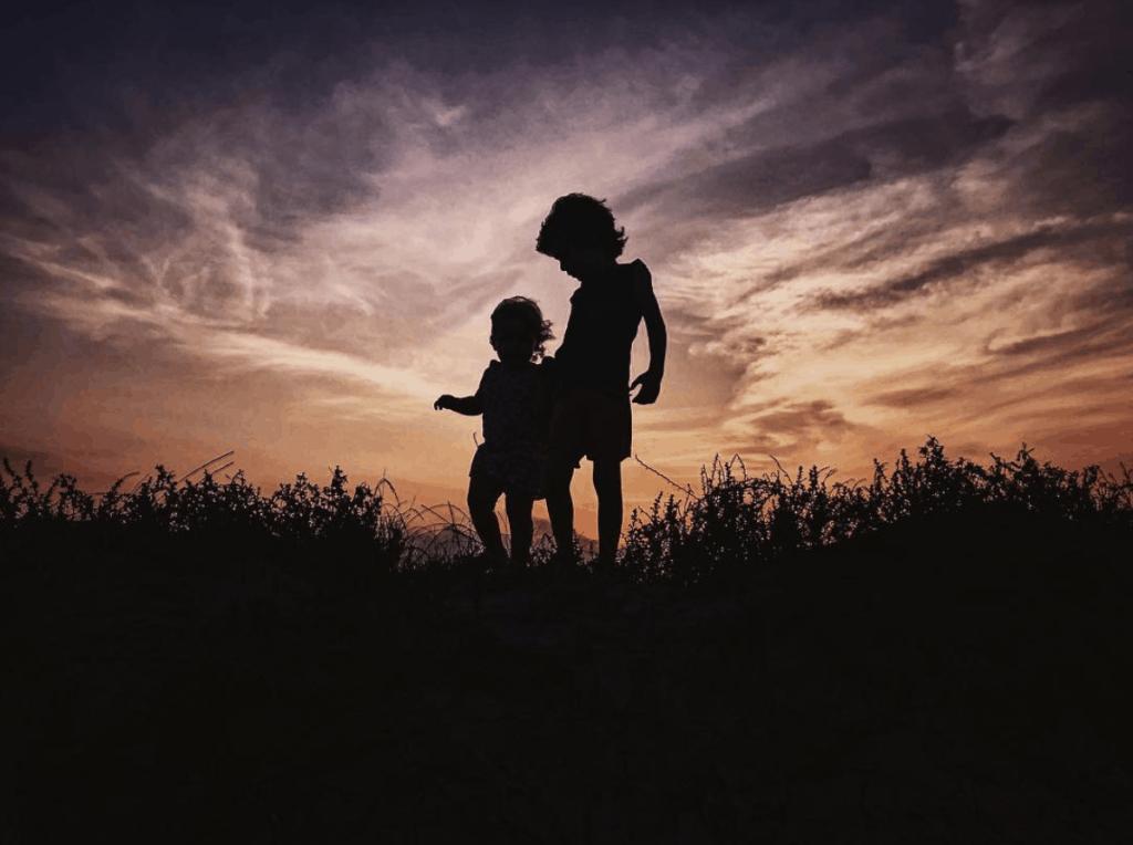 Silueta de hermanos pequeños al atardecer