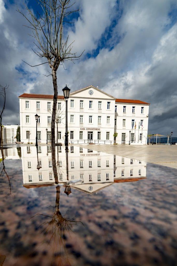 Edificio y nubes reflejados en agua