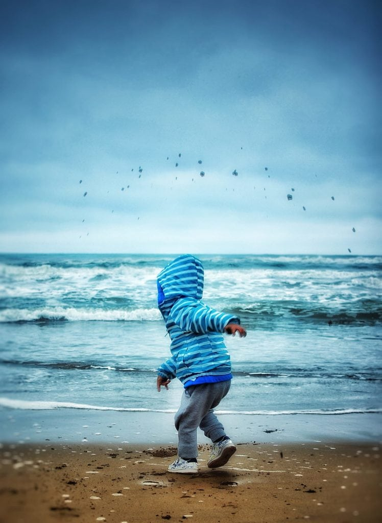 Niño jugando en la orilla de la playa con frío
