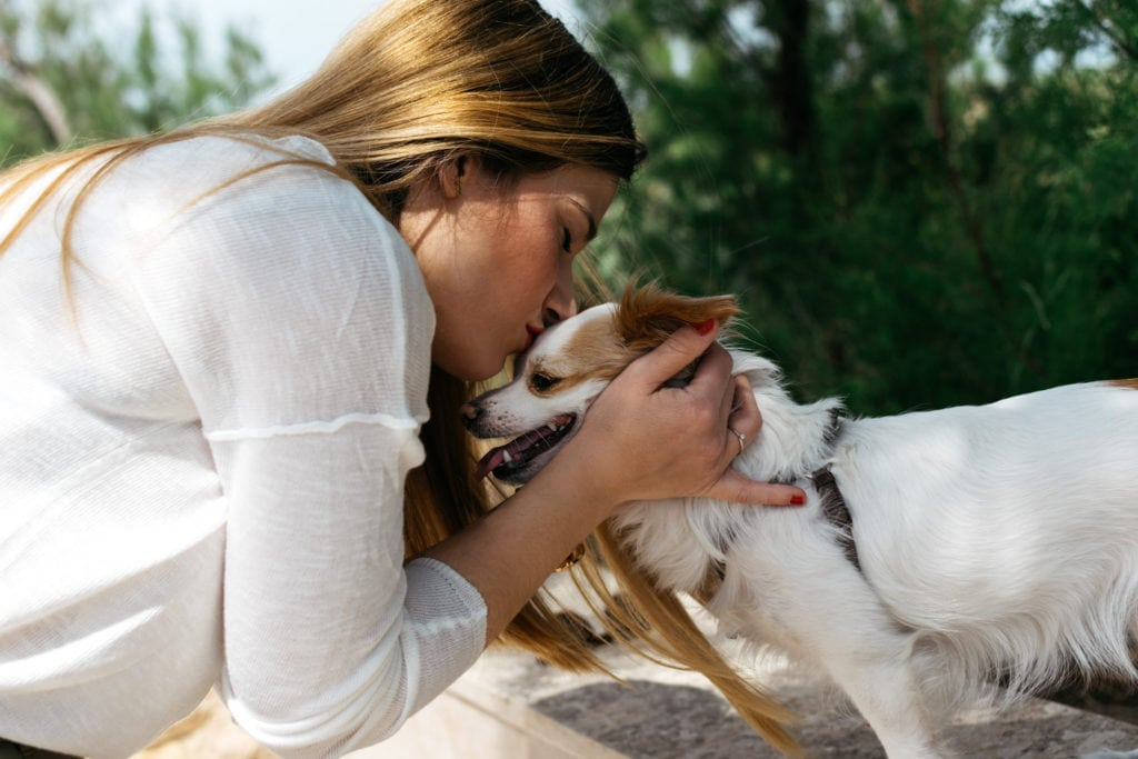 Mujer besando a un perro