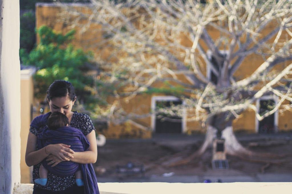 madre con bebé en brazos y árbol al fondo