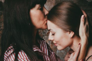 Madre dando un beso a su hija en la frente