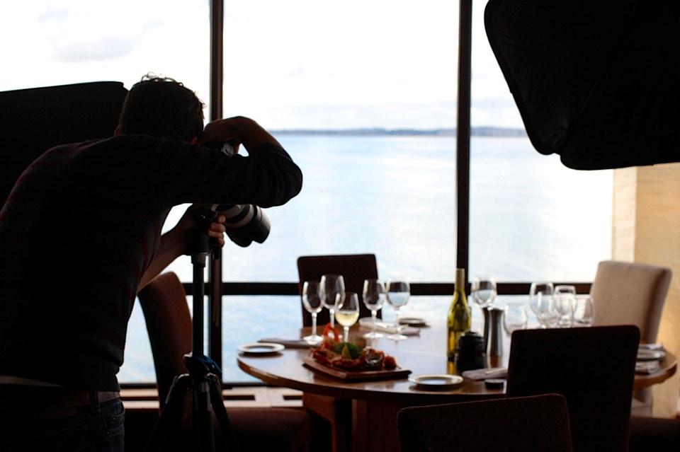 Fotógrafo haciendo fotos en una mesa de restaurante