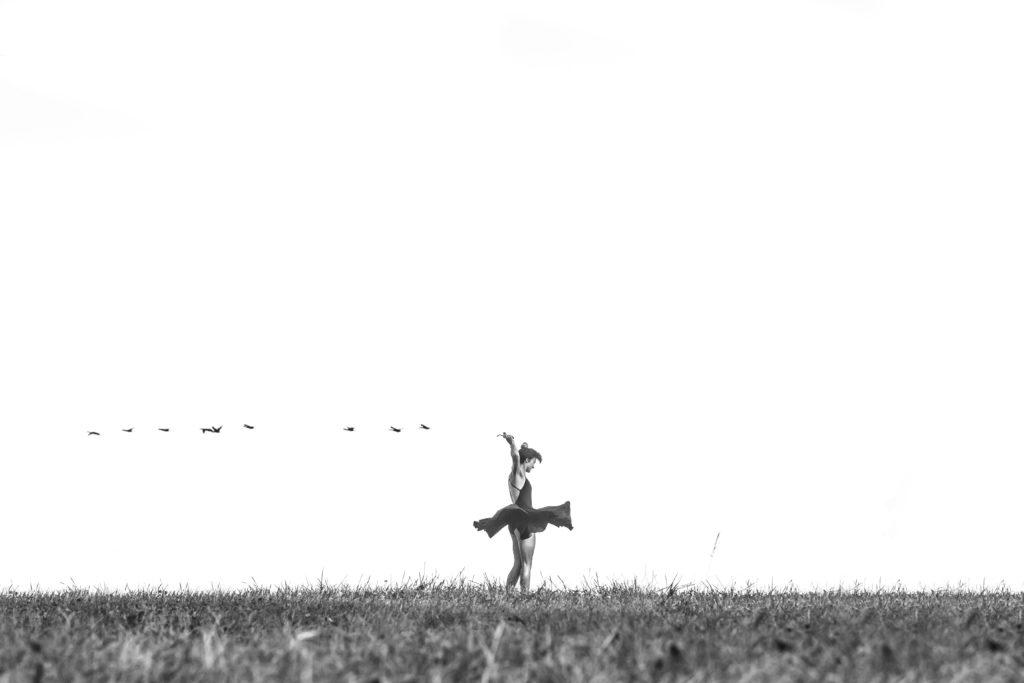 Bailarina en medio del campo con pájaros volando