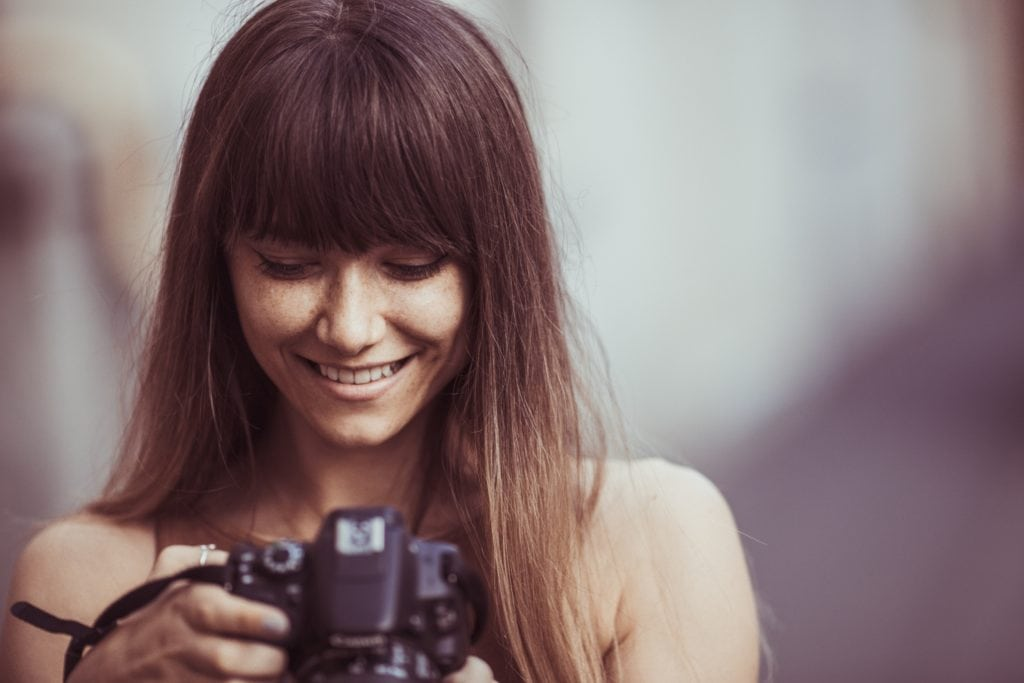 Mujer joven sosteniendo cámara mientras sonríe