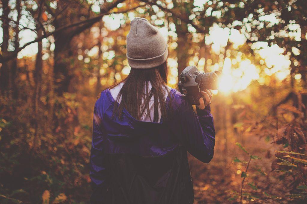 chica con cámara en mano de espaldas y a contraluz