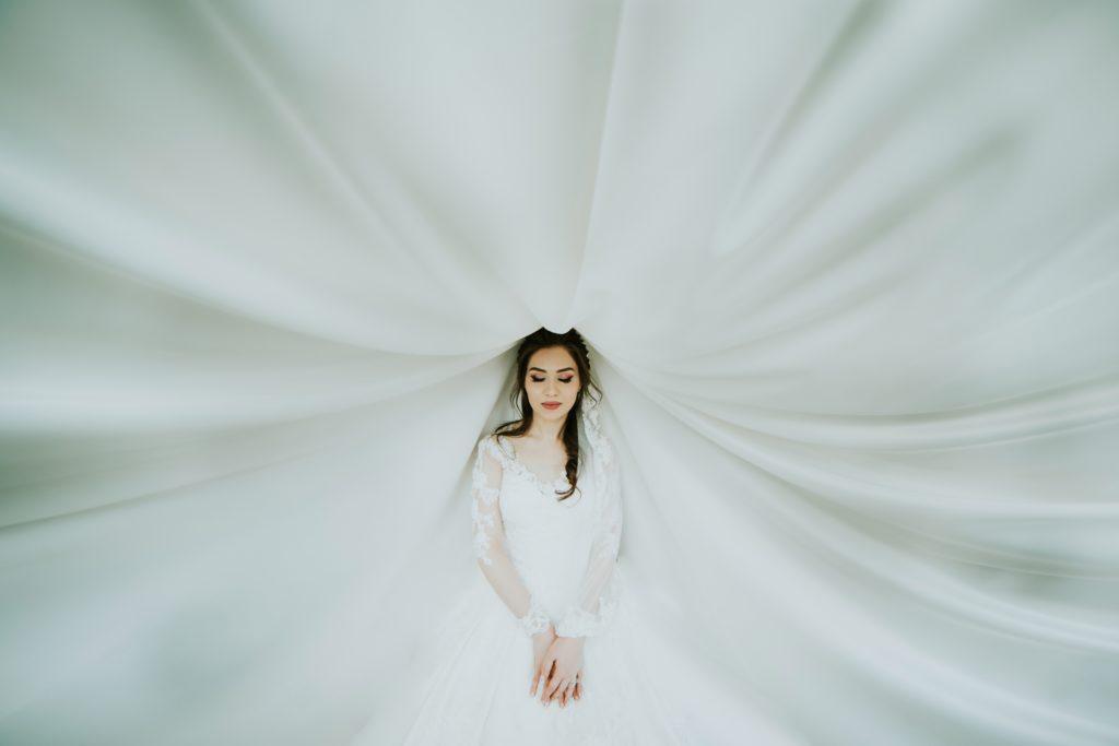 Novia fotografiada con su vestido de fondo.