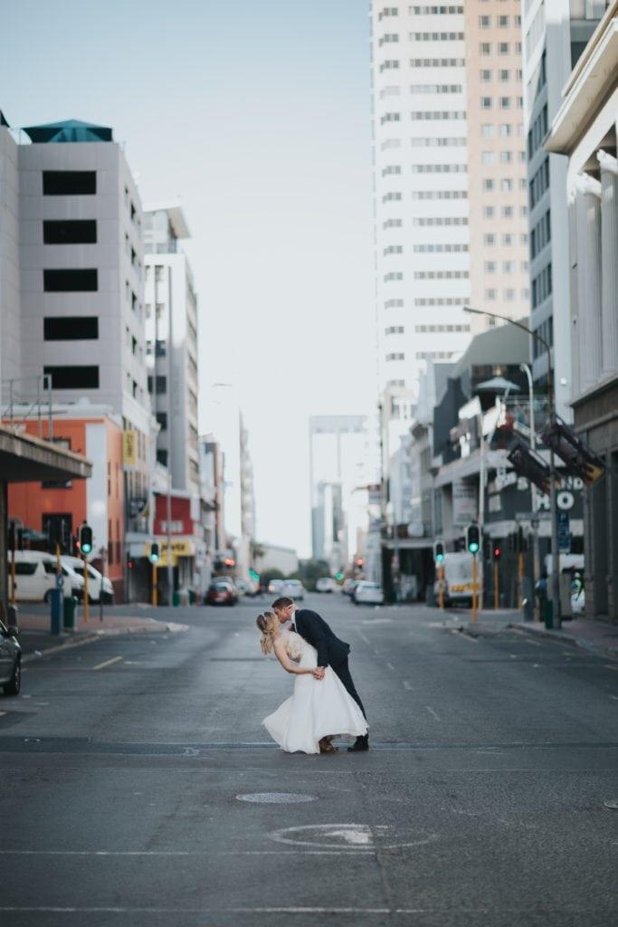 Pareja de novios besándose en medio de la calle