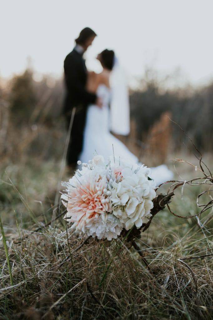 Flores con novios al fondo desenfocados