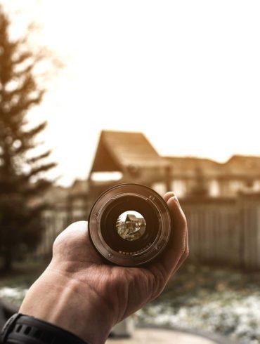 Vista de una casa a través de un objetivo sostenido por una mano