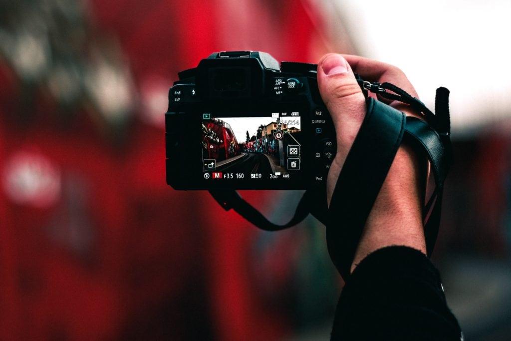 Mano sosteniendo cámara con vista de pantalla LCD en Manual