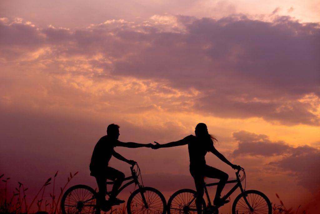 Silueta de pareja montada en bici en un atardecer de verano