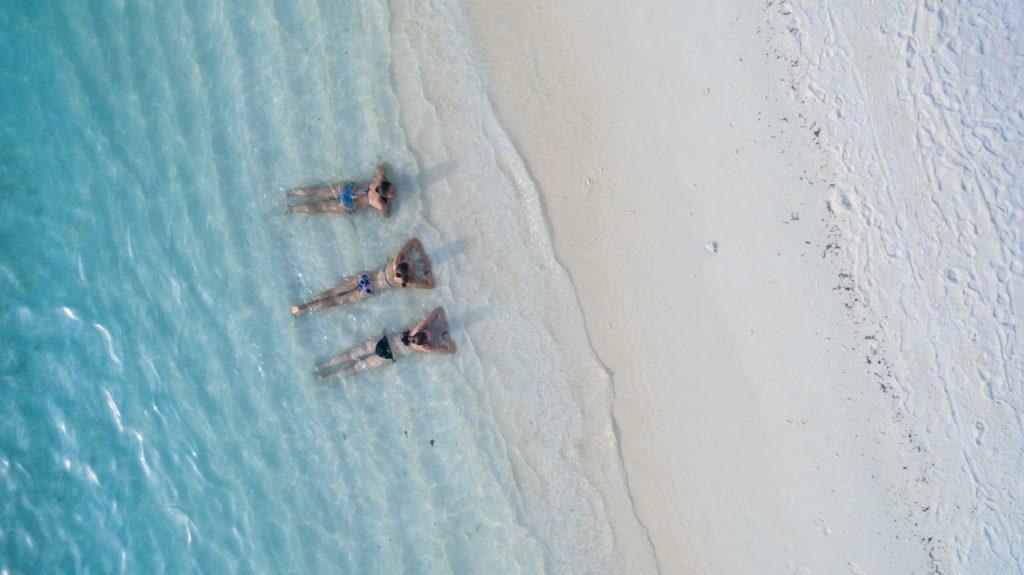 Tres chicas en la orilla playa fotografiadas con un dron