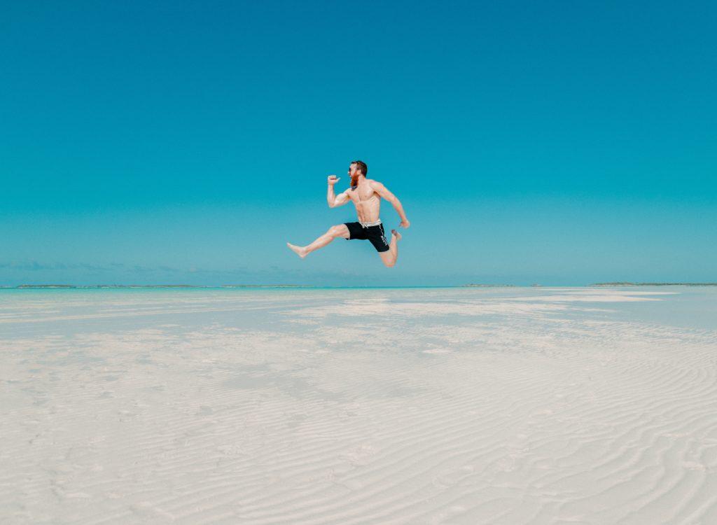 Chico saltando en la playa