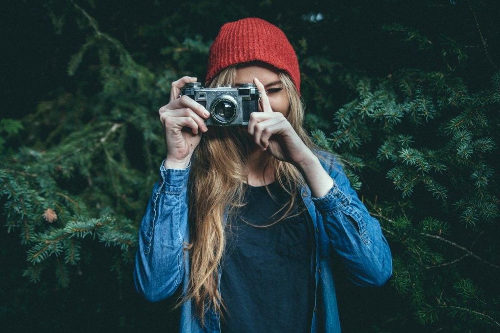 Chica con gorro rojo sosteniendo una cámara