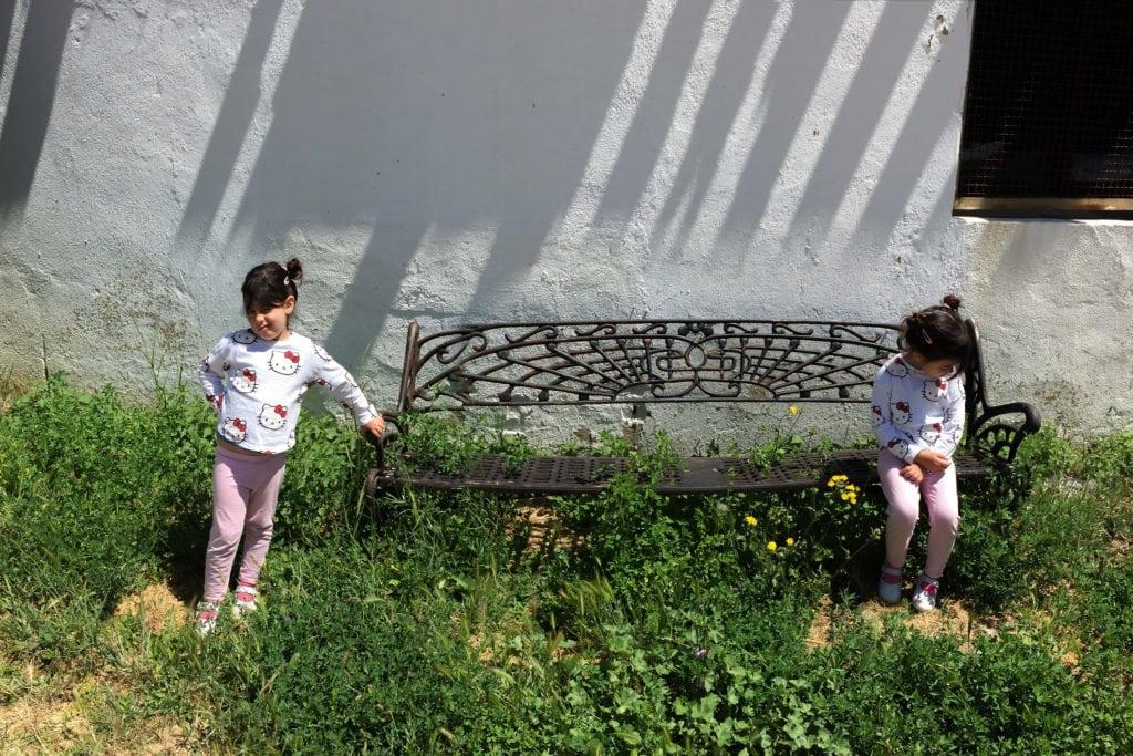 Niña clonada en un banco con fachada de fondo