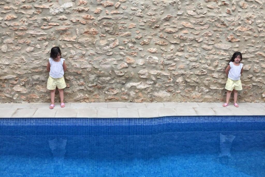 Niña clonada en piscina con fachada de piedra al fondo