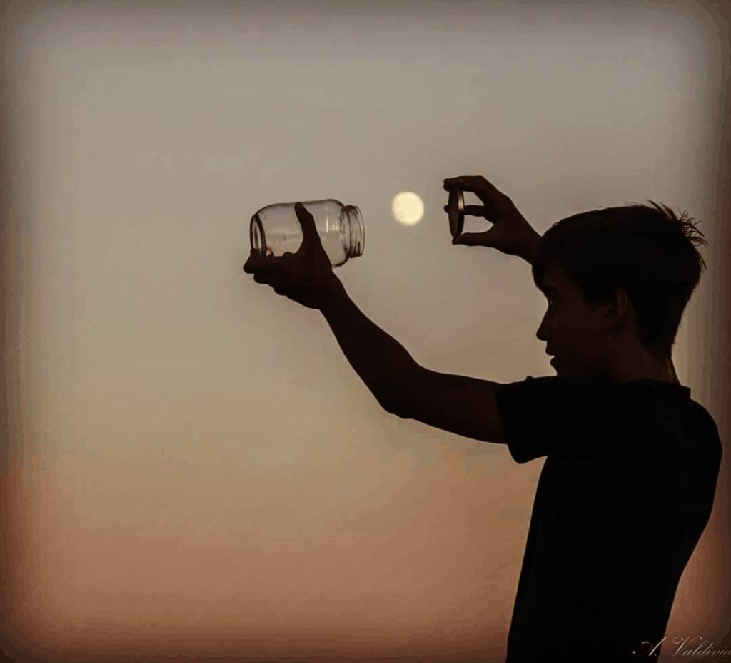 Silueta de niño cazando la luna con un bote de cristal