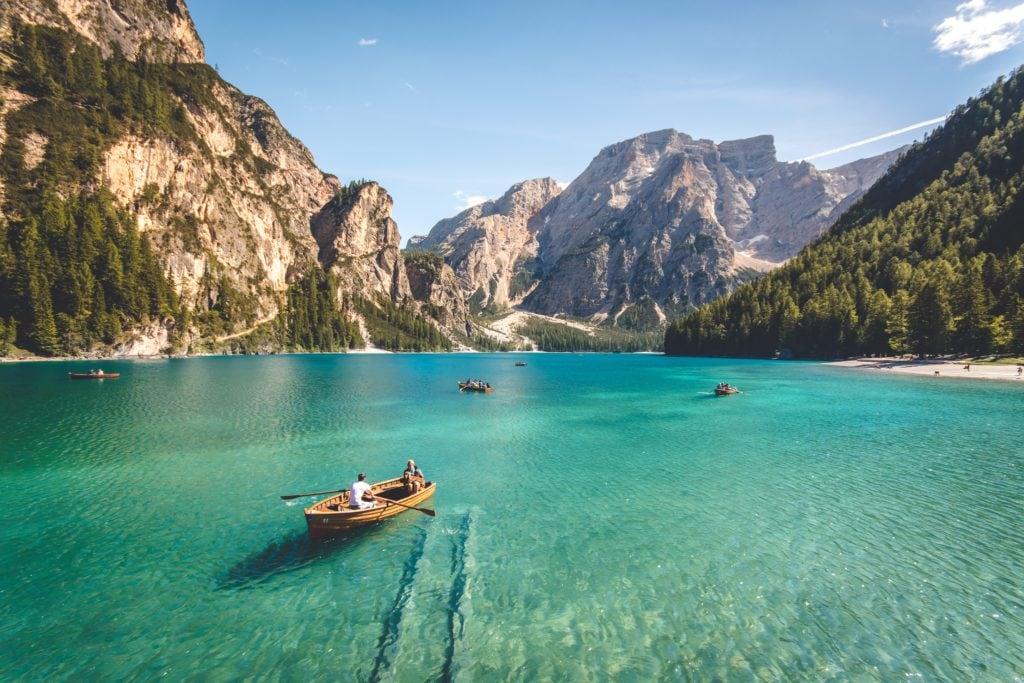Lago rodeado de montañas con barquitas