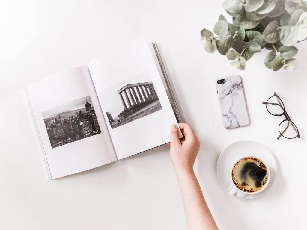 Libro de fotografía abierto, con mano pasando hojas y un café al lado