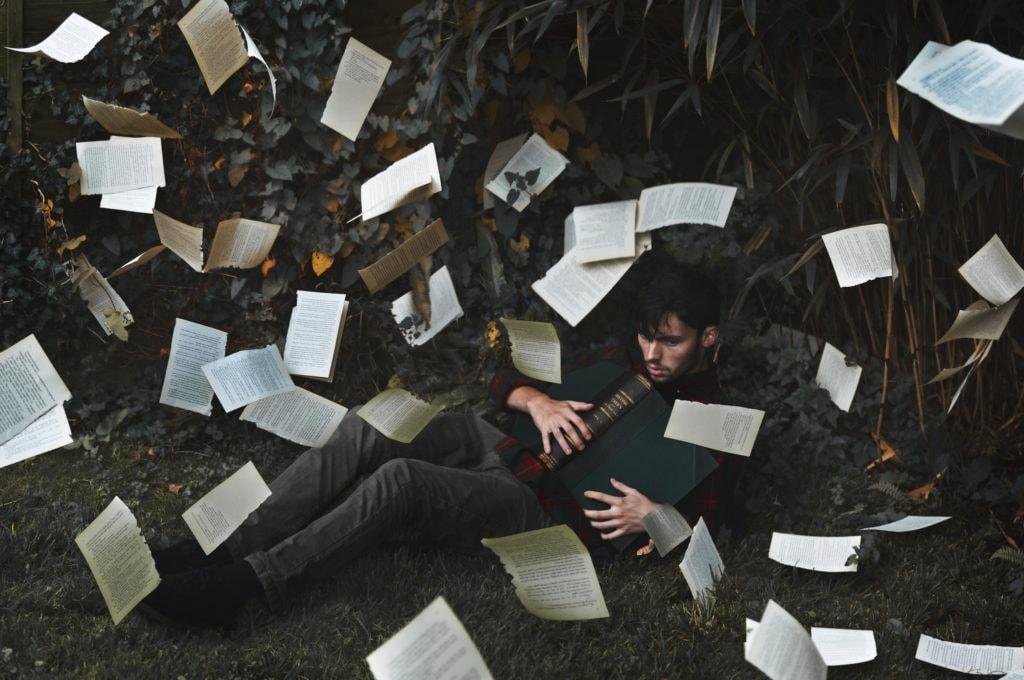 Chico sentado en la hierba con libro y muchas hojas del libro volando