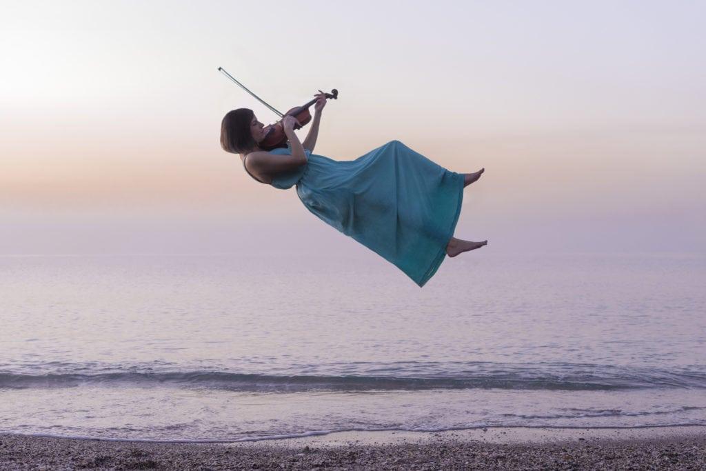 Violinista volando en la orilla de la playa