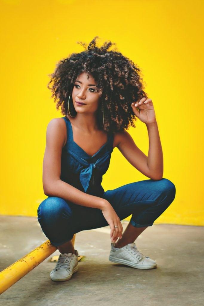 Mujer de pelo afro con fondo amarillo