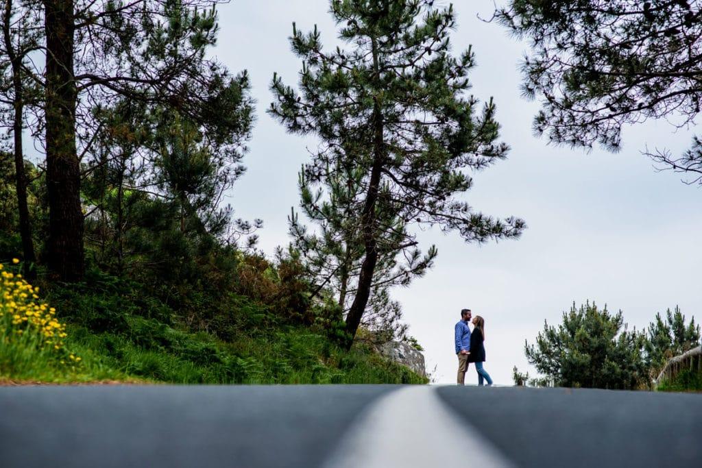 pareja en carretera con bosque de fondo