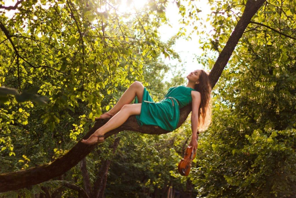 Mujer tumbada en la rama de un árbol