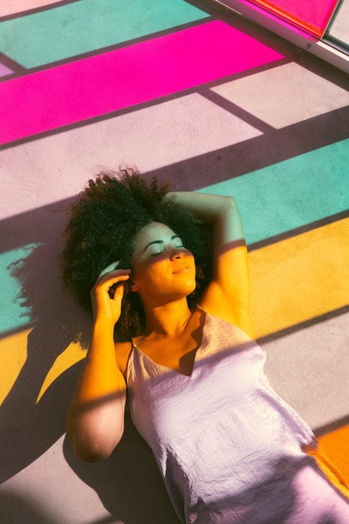 Mujer tumbada con sombras de colores sobre ella