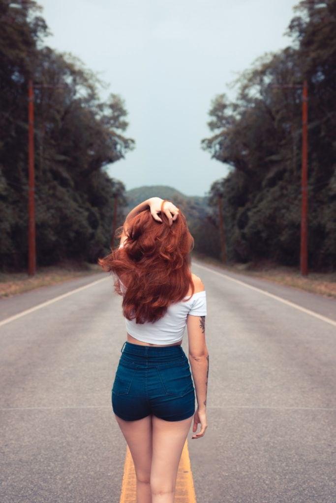 Chica pelirroja en carretera de espaldas