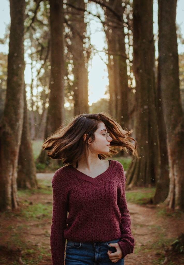 chica joven en bosque con pelo en movimiento