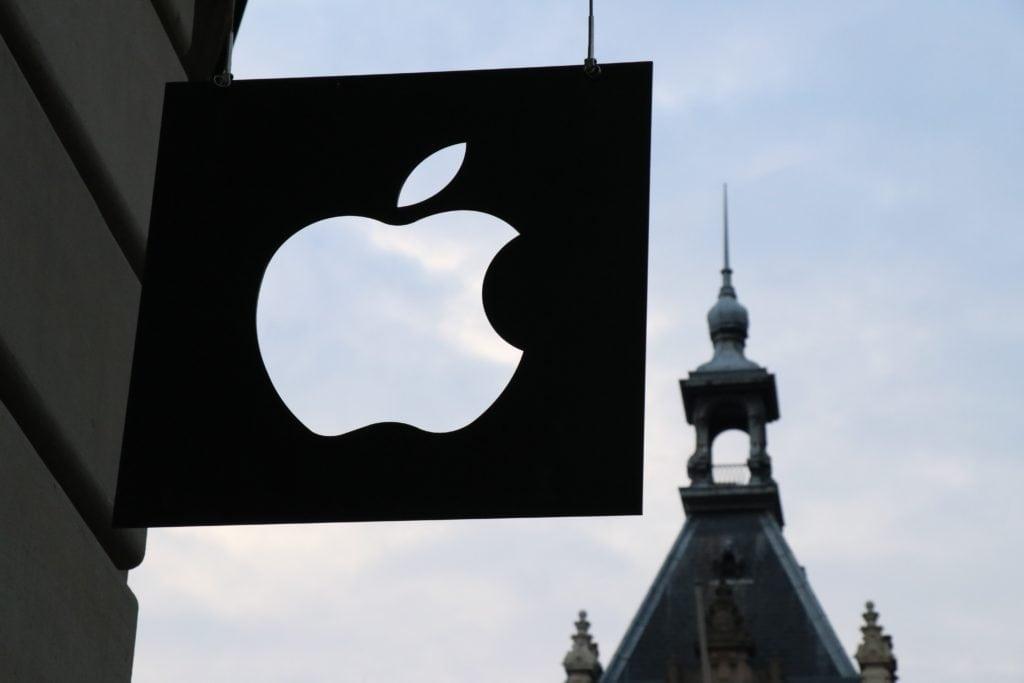 Letrero con logo de apple y torre al fondo